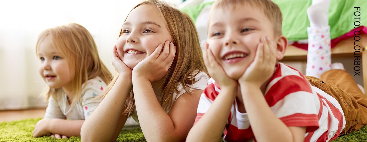 3 barn som ligger på gulvet og smiler